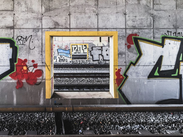 Berlin Architecture Art And Craft Building Exterior Built Structure Communication Creativity Day Graffiti Human Representation Mural No People Outdoors Rail Transportation Railroad Track Street Art Text Track Train Station Transportation Wall - Building Feature Western Script