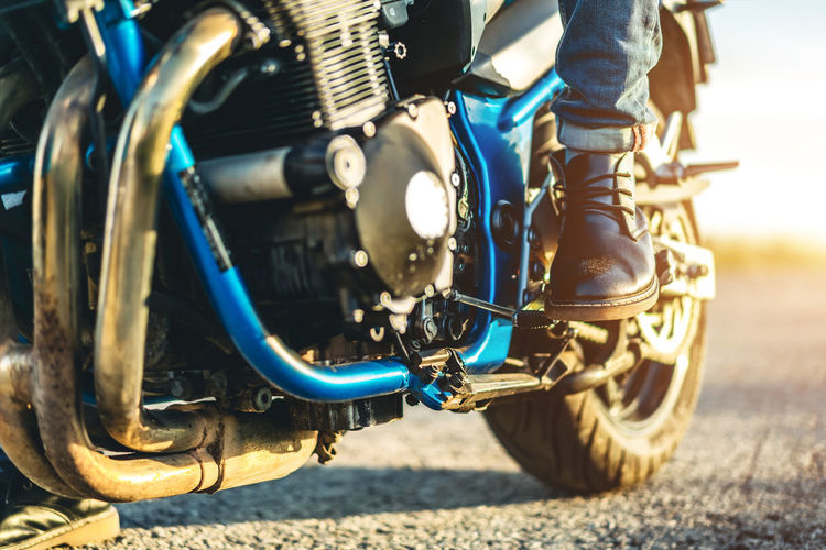 Low section of man riding motorcycle on road