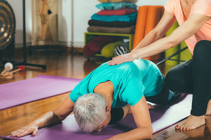 Mid adult daughter assisting mother while practicing yoga at spa