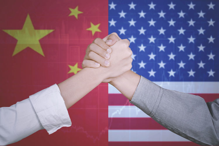 Cropped image of people holding hands against chinese and american flags