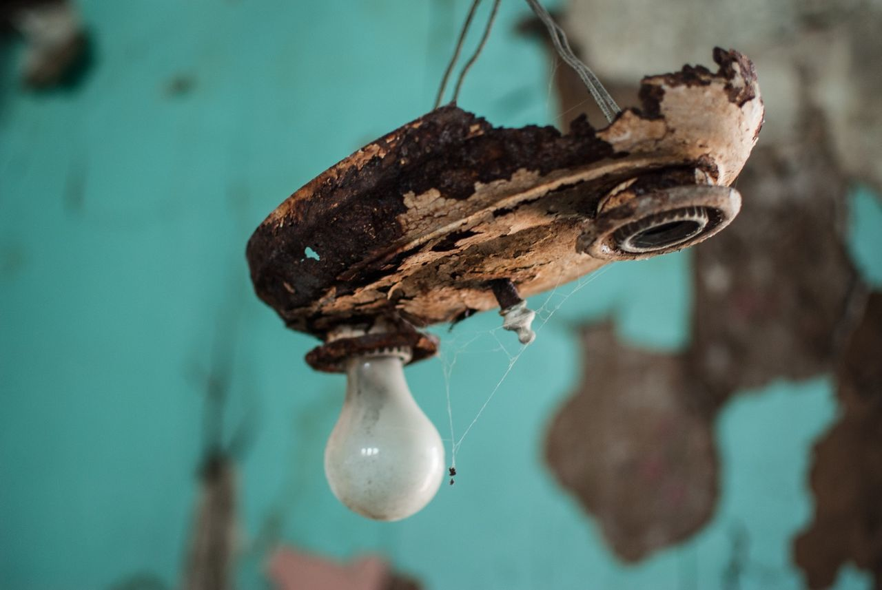 Close-up of old light bulb in abandoned house