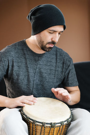 Man playing drum while sitting in studio