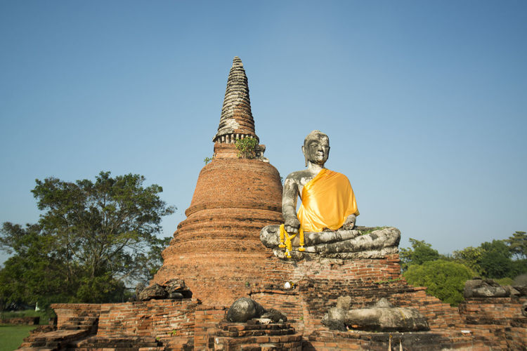 Low angle view of buddha statue by temple at ayutthaya historical park