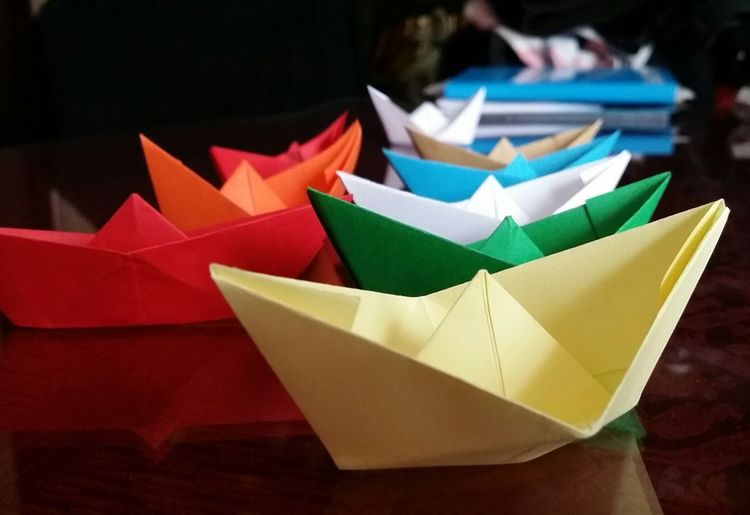Row of colorful paper boats on table