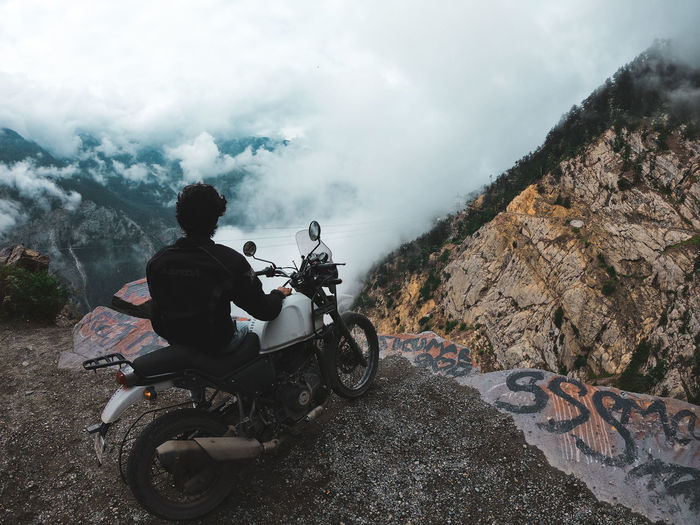 Man riding motorcycle on mountain against sky