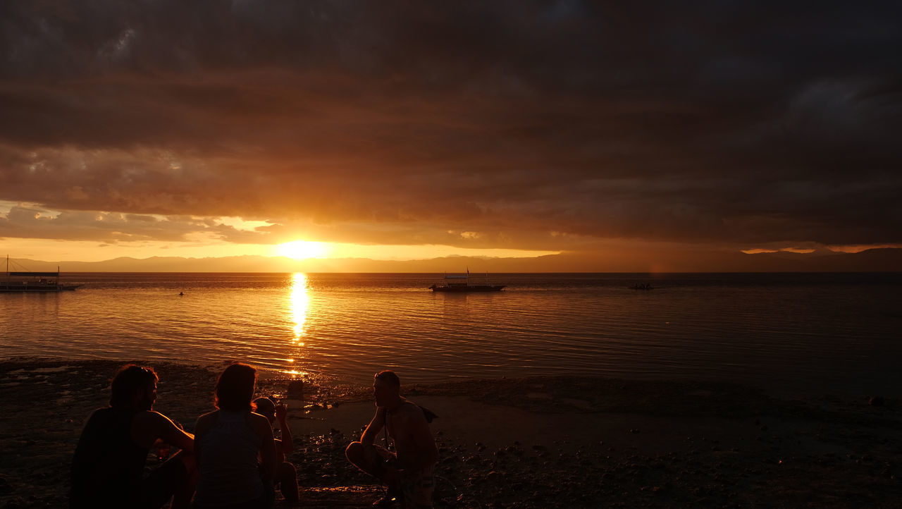 sunset, water, beauty in nature, sky, silhouette, nature, orange color, scenics, sea, cloud - sky, sun, real people, beach, tranquil scene, idyllic, tranquility, lifestyles, horizon over water, men, reflection, leisure activity, outdoors, women, togetherness, vacations, people