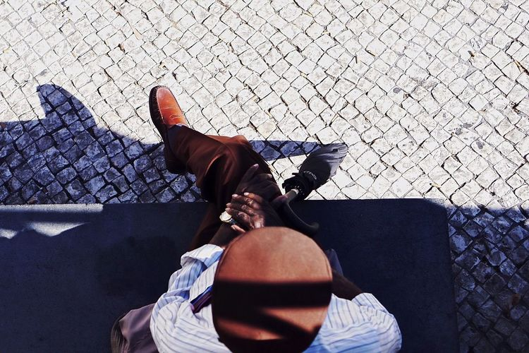 High angle view of man relaxing on seat at cobbled street