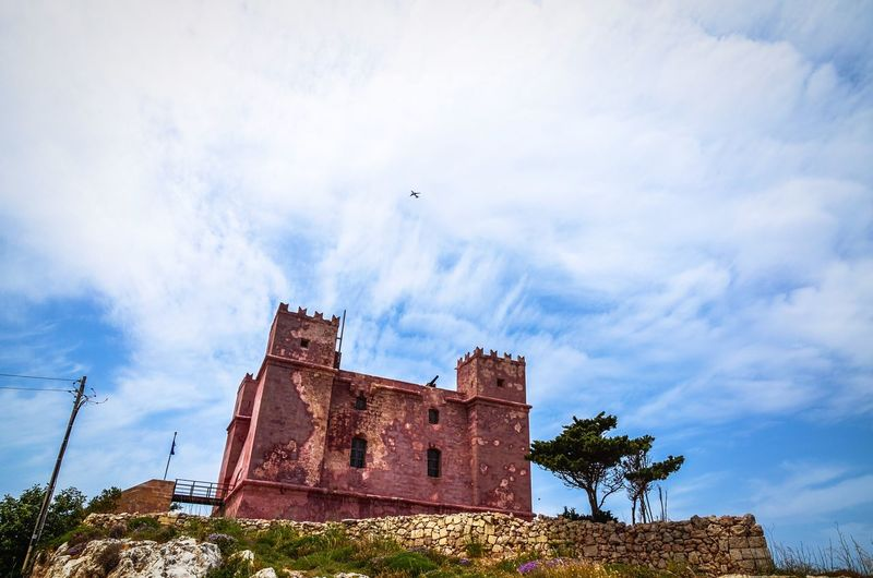 The Red Tower of Saint Agatha in Mellieha Bay, Malta, as a plane soars on the puffy clouds. Malta St Agatha's Red Tower Mellieha Bay Mellieha Fort Castle Fortification Fortress Sky Clouds Plane Flying Low Angle View Summer Travel Mediterranean  Flight Path Saint Agatha Stone Wall Architecture Building Vacation