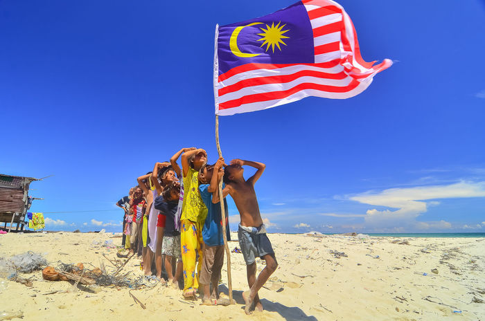 independence Day concept - a group of bajau laut kids running at sea shore holding a Malaysian flag 31 August Blue Cloud Day Fun Leisure Activity Lifestyles Malaysia Merde Multi Colored Nature Outdoors Parasol Sky Sunlight Sunny Tourism Tourist Vacations Wind