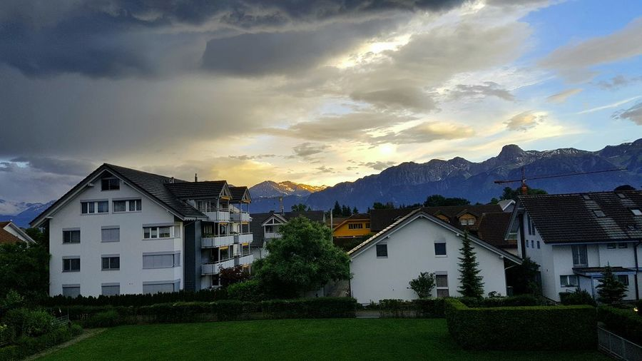 Buildings by mountains against cloudy sky during sunset