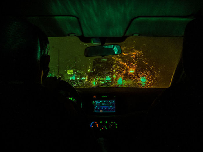 Rear view of people seen through car windshield