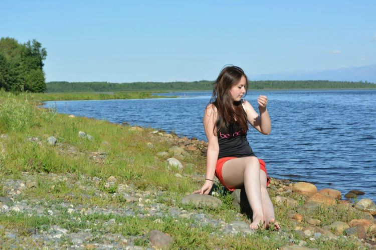 Water Leisure Activity Lifestyles Person Grass Young Women Casual Clothing Full Length Young Adult Clear Sky Long Hair Nature Summer Day Scenics Tranquil Scene Beauty Weekend Activities Beauty In Nature Non-urban Scene