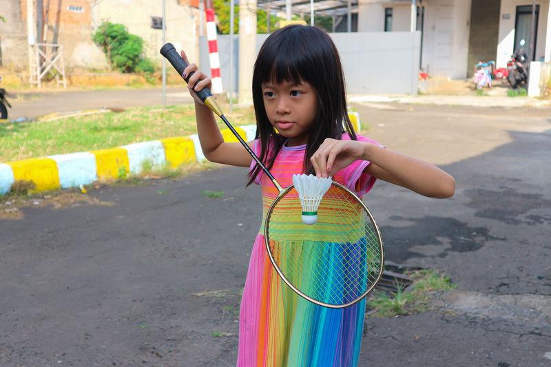 Full length of cute girl holding multi colored umbrella
