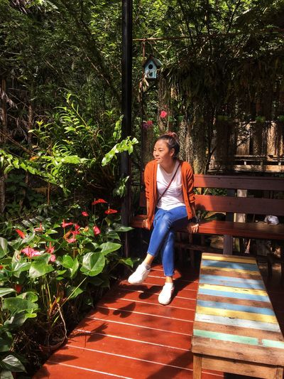 Full length of woman sitting on bench by plants