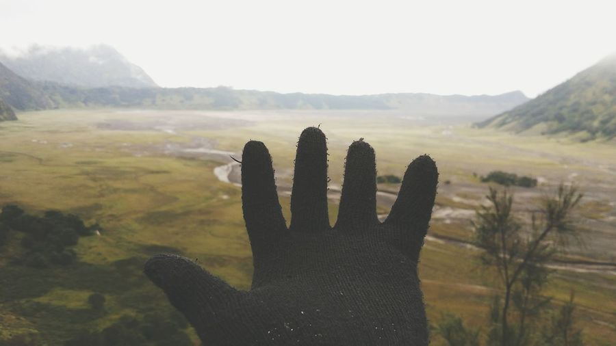 Close-up of hand wearing glove against landscape