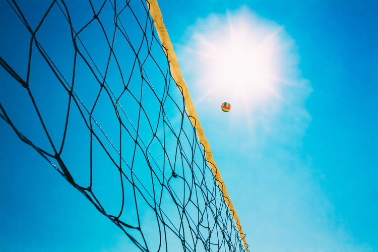 Low angle view of volleyball net against clear blue sky