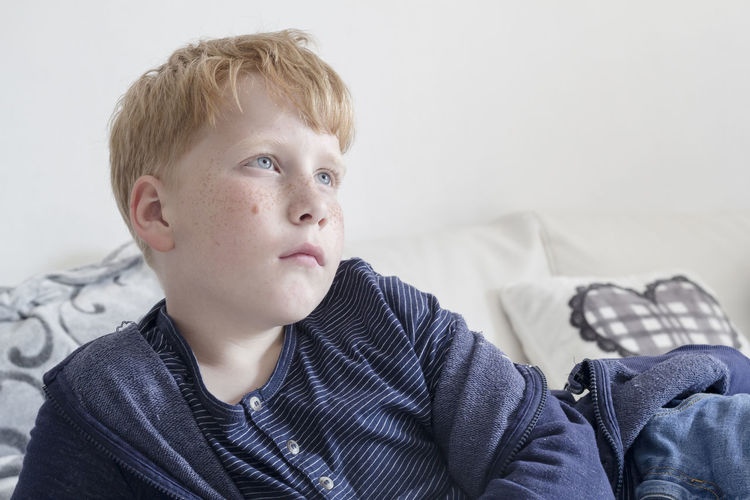 Copy Space Bed Blond Hair Blond Hair And Blue Eyes Boys Causal Clothing Childhood Close-up Day Elementary Age Freckles Home Interior Indoors  One Boy Only One Person People Portrait Real People Sitting Watching