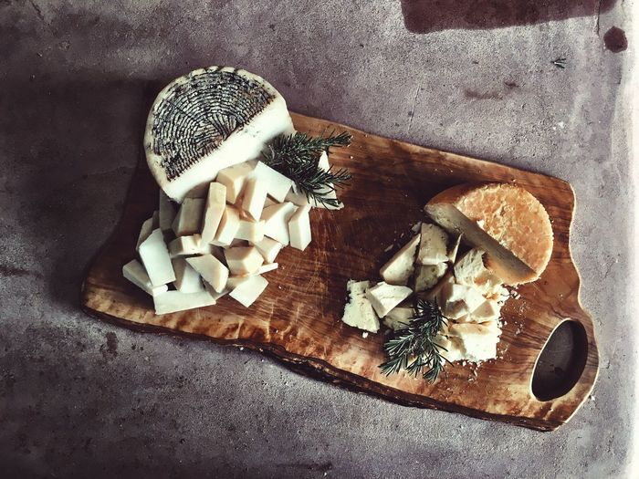 High Angle View Of Cheese Plate On Wooden Cutting Board