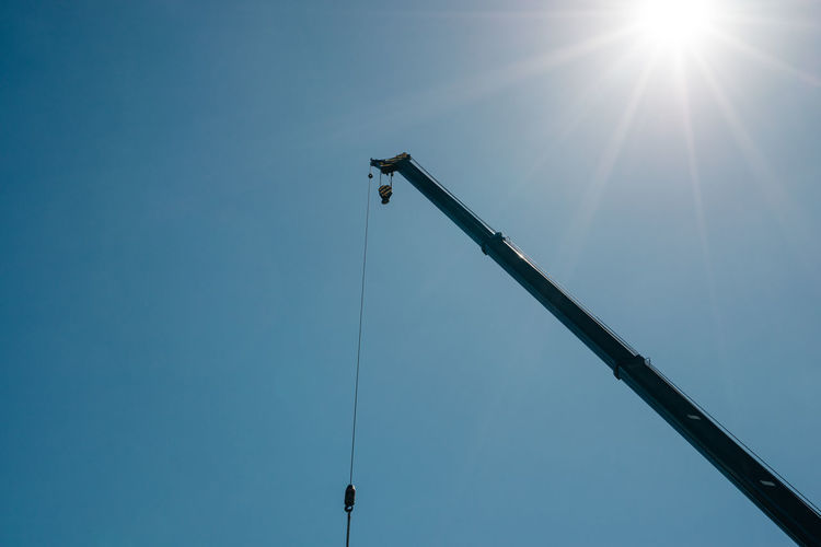 Construction Crane Boom with Sun in the background. Construction Construction Site Construction Crane Construction Machinery Industrial Industry Machinery Blue Building Building Crane Clear Sky Crane Day Hoist Lift Low Angle View No People Outdoors Progress Sky Sun Sun Rays Sunlight