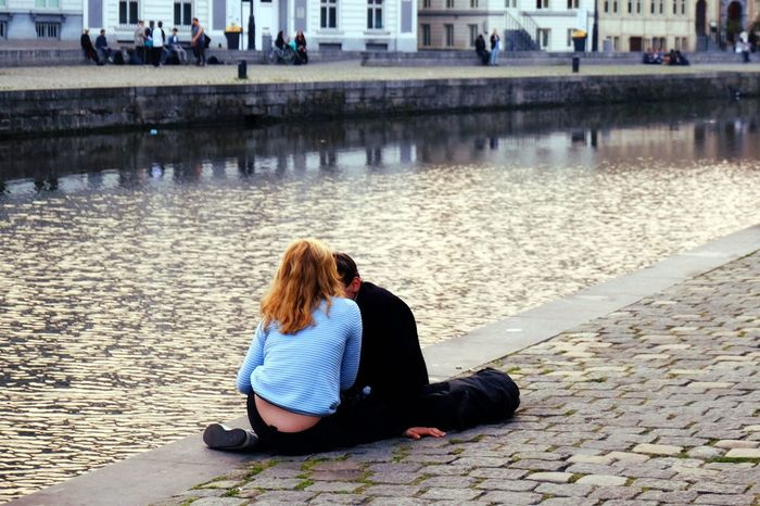 Canal Casual Clothing City City Life Couple Europe Flanders Ghent He And She Leisure Activity Long Hair Love Outdoors Pavedment Relaxation River Sitting Water Youth
