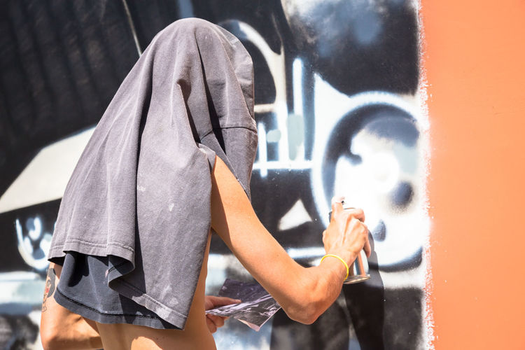 Adult Casual Clothing Close-up Creativity Day Females Focus On Foreground Graffiti Holding Leisure Activity Lifestyles Metal Obscured Face One Person Outdoors Real People Side View Technology Wall - Building Feature Women