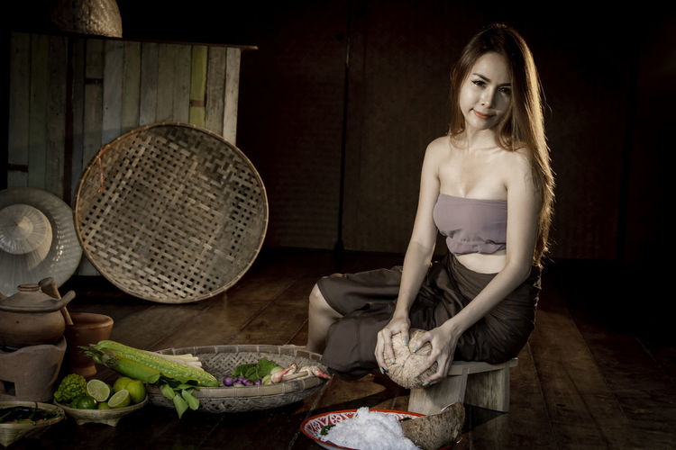 Portrait of woman wearing traditional clothing grating coconut at home