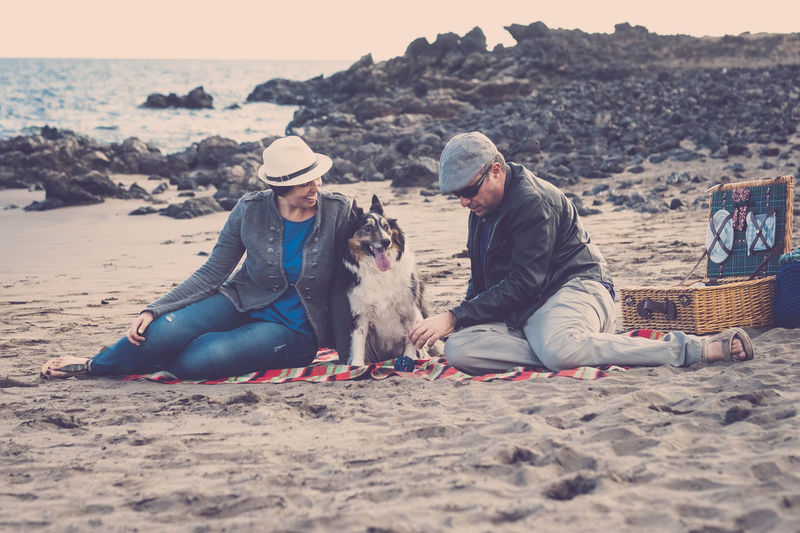 Couple with dog sitting on shore at beach