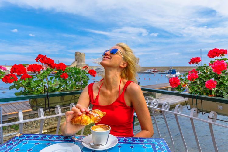 Woman wearing sunglasses and red flowers on table against sky