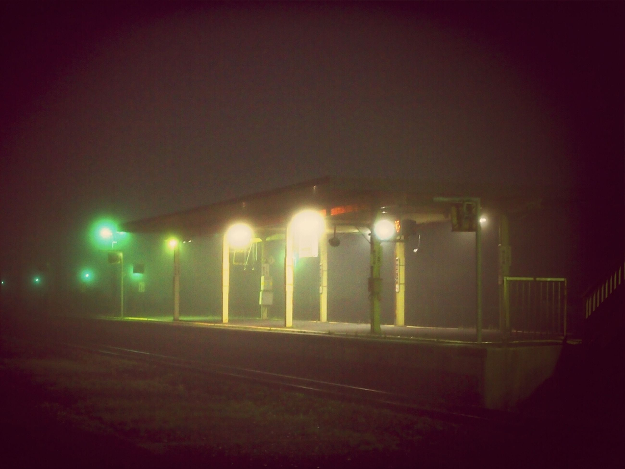 illuminated, night, lighting equipment, street light, light - natural phenomenon, copy space, built structure, architecture, dark, building exterior, glowing, no people, outdoors, electric light, street, road, long exposure, green color, clear sky, light
