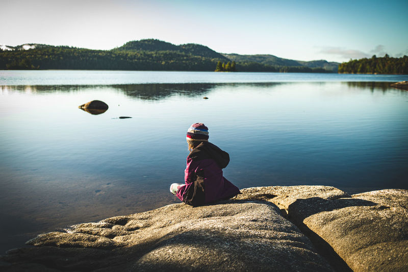Girl sitting on rock by lake against sky