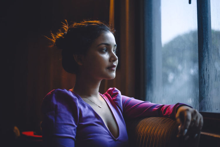 Portrait of young woman looking away against window