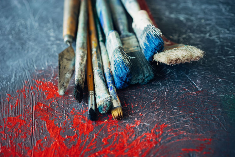 set of brushes on an abstract painted surface with red spots Painted Red Set Abstract Backgrounds Blue Brushes Close-up Day Indoors  No People Surface Level