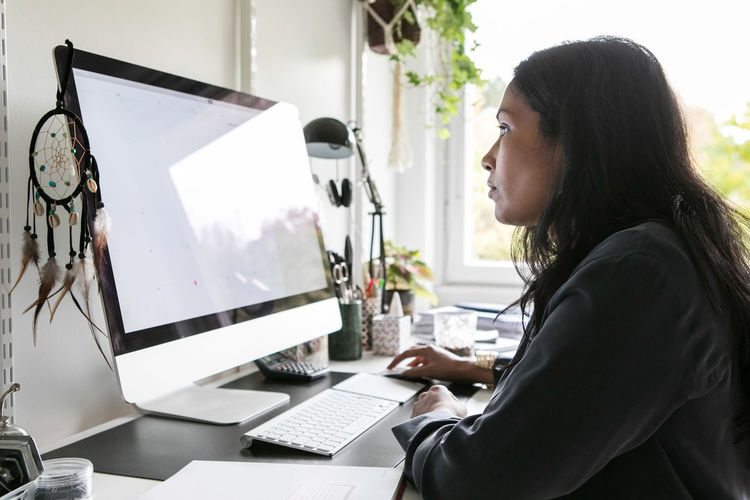Side view of woman using laptop
