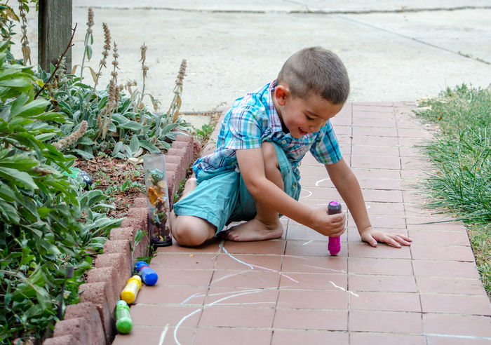 who needs a tablet when you can have a entire side walk? little boy with sidewalk chalkKids Summertime Active Kids Art Boys Childhood Creative Day Drawing Kids Having Fun One Person Outdoors People Playing Outdoors Real People Sidewalk Chalk