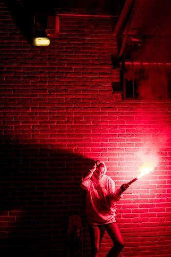 Full length of man standing against illuminated wall