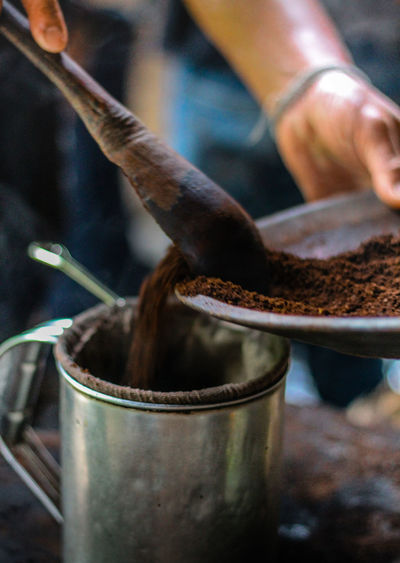 Cropped hand putting roasted coffee bean powder in container