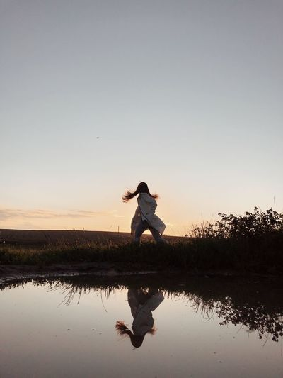 Silhouette woman jumping on lake against sky during sunset