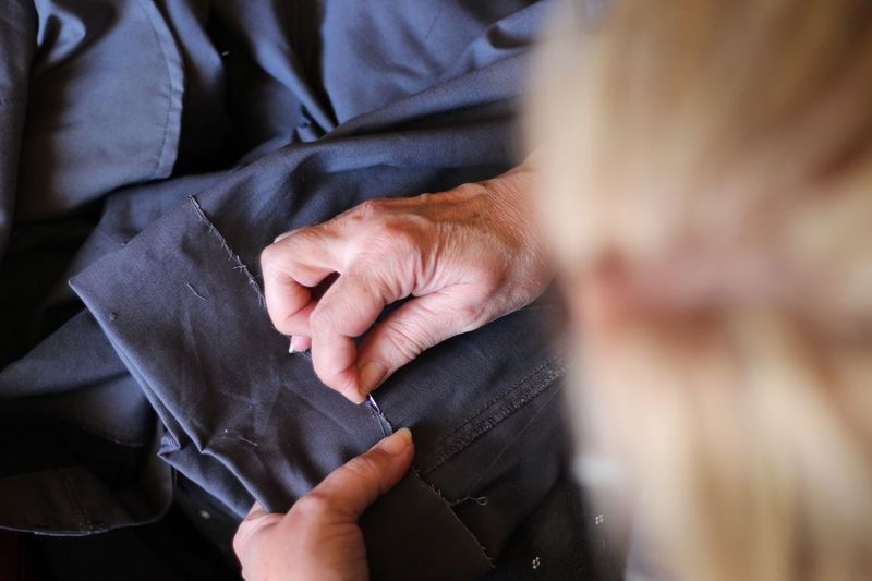 Close-up of woman stitching fabric
