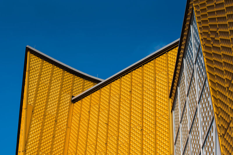 Low angle view of yellow building against clear blue sky