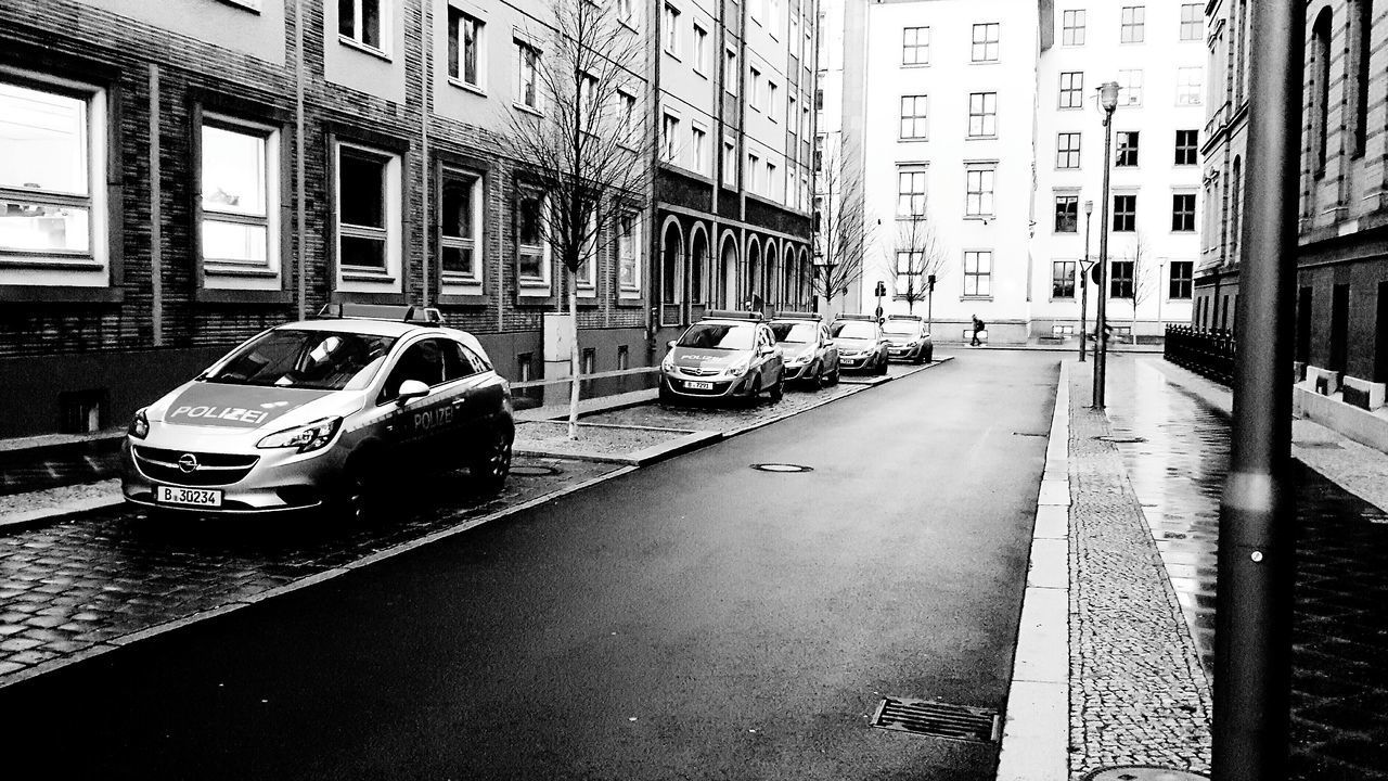 car, motor vehicle, mode of transportation, transportation, city, building exterior, land vehicle, built structure, architecture, street, road, day, building, residential district, city street, travel, no people, motion, city life, on the move