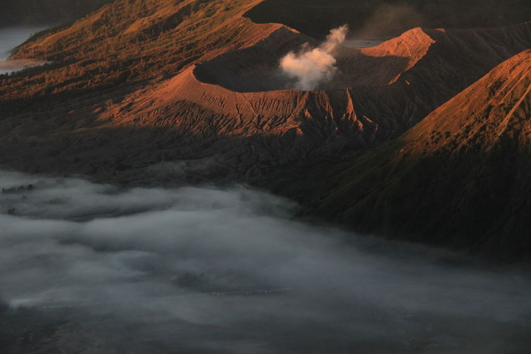 Scenic view of volcanic mountain against sky. thick fog enveloped mount bromo