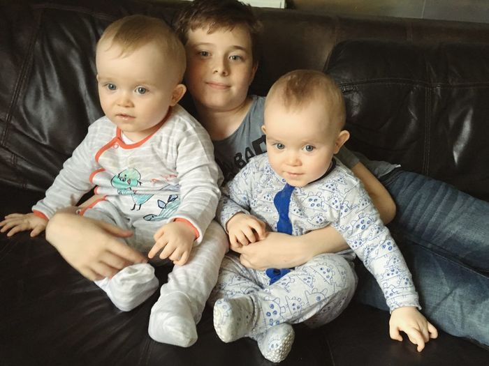 Portrait of brother with twin baby boys relaxing on sofa at home