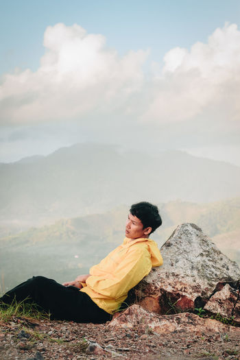 Side View Of Man Sitting On Mountain Against Cloudy Sky