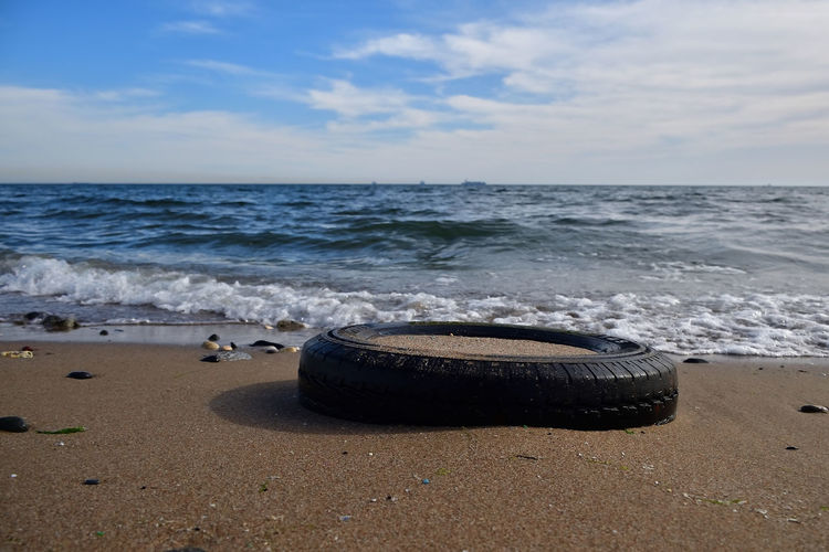 Tire in sand on shore at beach