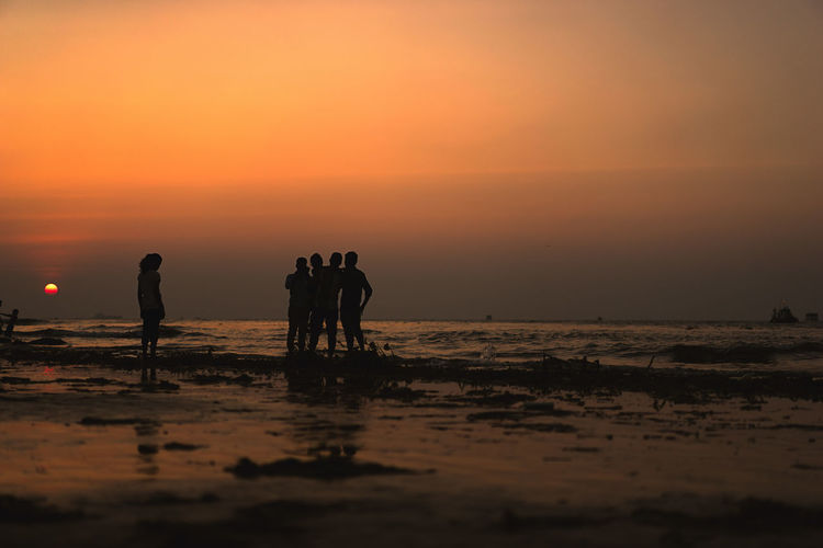 Silhouette people standing on beach against sky during sunset