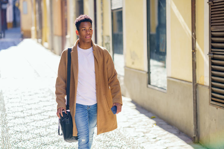 Portrait of young man walking on footpath