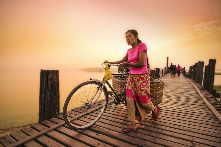 Woman with bicycle walking on pier over sea against sky during sunset