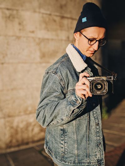 Midsection of man photographing against wall