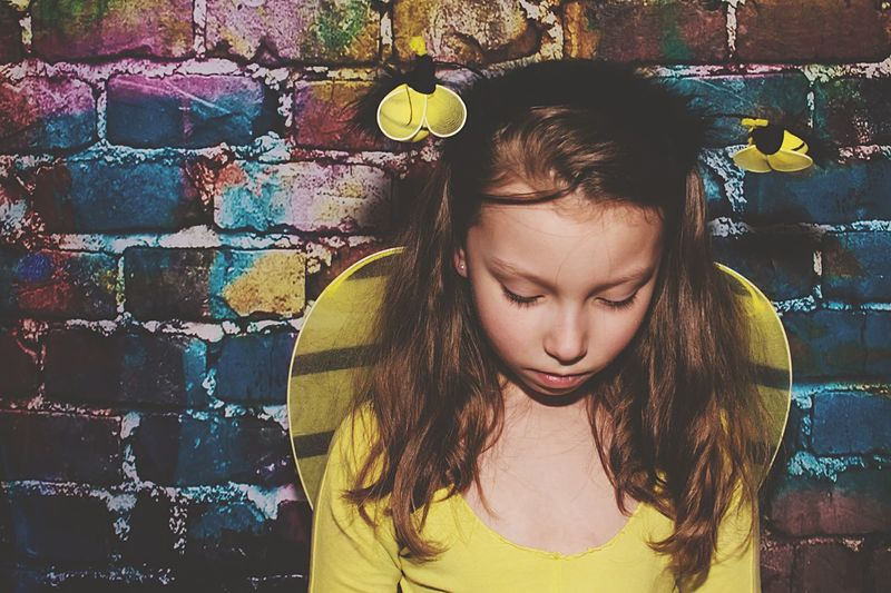 Sad girl wearing bumblebee costume standing against wall
