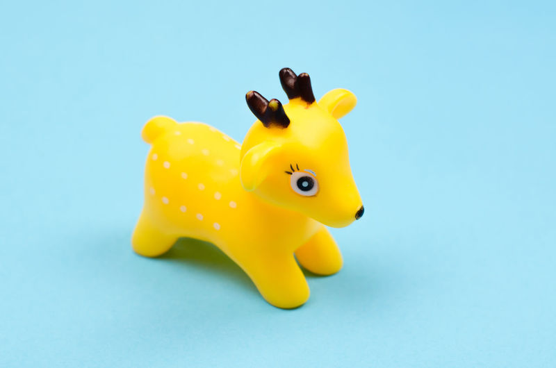 Close-up of yellow toy over blue background